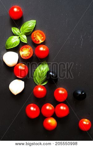 Tomatoes basil leaf mozarella cheese and black olives. Fresh vegetables and fresh herbs over dark chalk board background. Food ingredients