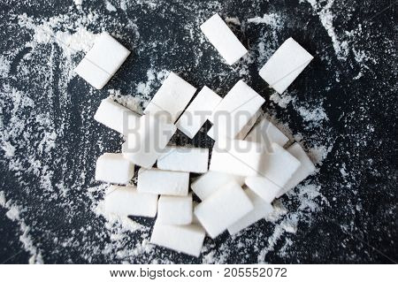 Unhealthy food concept - sugar and flour on a black background. Dangerous high amount of sugar in food. Carbohydrates sources top view