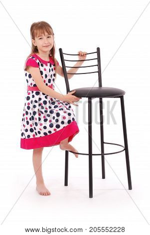 Portrait of adorable smiling little girl and black chair isolated on a white background with soft shadow