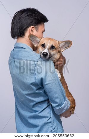 A man snuggling and hugging his dog close friendship loving in studio background
