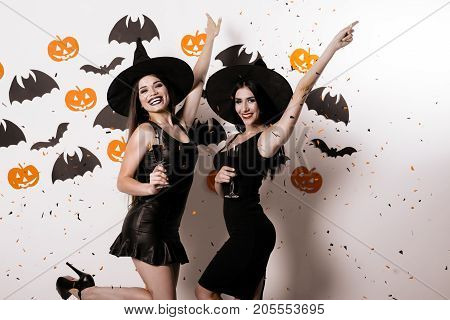 Two joyful models in sexy suits witches posing against white background with bats, holding glasses with wine in hands