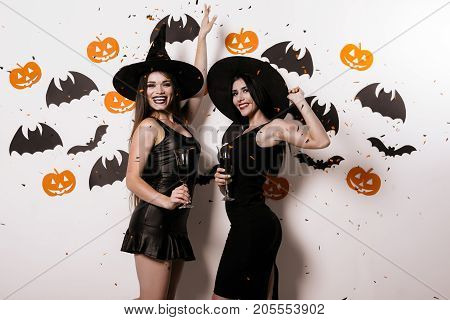 Two models are posing on a white background with volatile mice dressed in black sexy dresses and witch hats. They hold glasses of wine and smile. Confetti is falling on them. poster