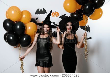 Halloween party. Two sexy models in sexy black dresses and witch hats posing with black and orange balloons. They are smiling