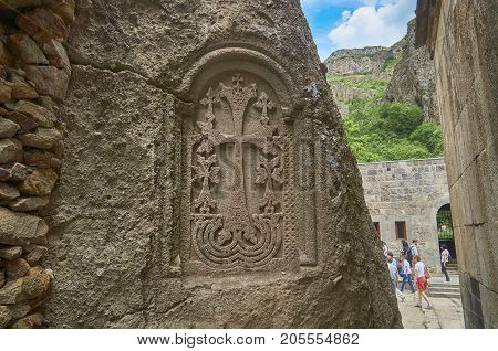 Armenia, monastery Geghard - 2017, June 12. Sacred armenian cross stone khachkar in the wall of ancient monastery.