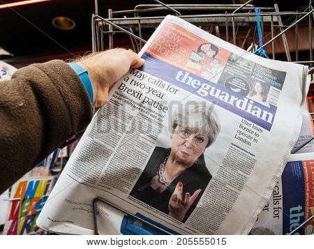 PARIS FRANCE - SEP 25 2017: Man buying latest The Guardian newspaper from press kiosk with Braking news from Theresa May British Prime Minister