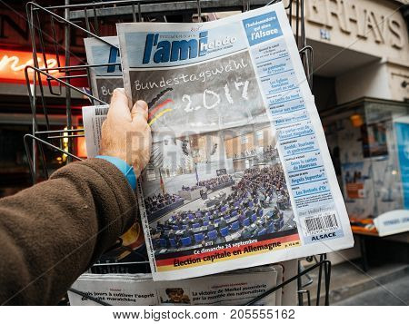 PARIS FRANCE - SEP 25 2017: Man buying latest newspaper with portrait of Bundestagswahl 2017 elections after election in Germany for the Chancellor of Germany the head of the federal government - Angela Merkel Wins