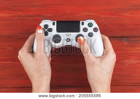 Sankt-Petersburg Russia September 24 2017: Sony PlayStation 4 dualshock game controller in gamers hand on wood background studio shot. Game console with a joystick. Home video game console