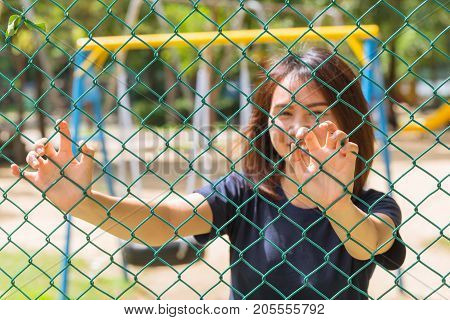 Asian Teen Smile Hand Catch Welded Wire Fence Inside Park