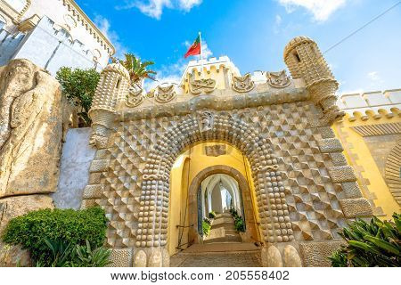 Spectacular arch entrance gate of Pena National Palace, in Portuguese Palacio da Pena or Castelo da Pena in Sintra. The palace is Unesco Heritage and one of the Seven Wonders of Portugal. Sunny day.