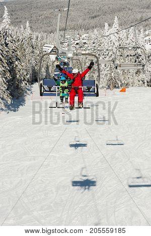 Little Boy With Ski Instructor Enjoying On Ski Lift, Color Image, Two People