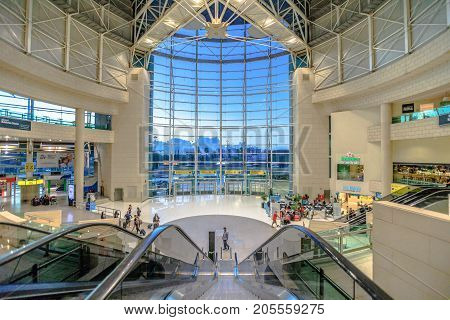 Lisbon, Portugal - August 28, 2017: Escalator at main entrance of Lisbon Humberto Delgado Airport. On background, large stained glass window overlooking Lisbon city. Travel and holidays concept.