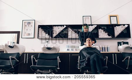 Woman sitting on salon chair while a hair stylist washing her hair. Hairdresser wiping the hair dry using a towel in the wash tub.