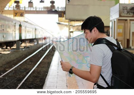 Rear view of handsome young Asian tourist exploring the map for right direction at the train station. Travel and tourism concept.