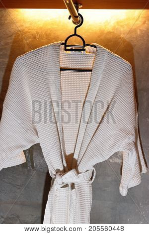 Bathrobe hanging on clothes hanger against warm white light background.