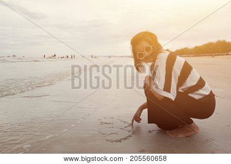 indy asian women smile draw heart shape on sand beach vintage color tone