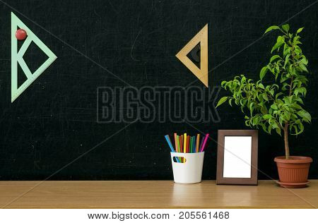 Teacher or student or office desk table. Education background. Education concept. Colour pencils in pencil holder green plant tree and photo frame on blackboard background.