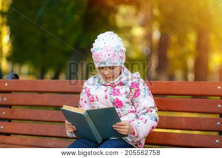 A Cute Child Is Reading A Book In The Park.