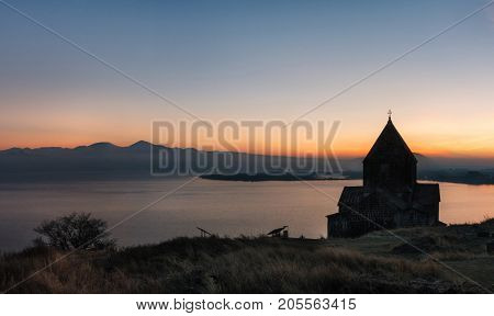 Panoramic view of the temple complex on the Sevan Lake at sunset Armenia. Silhouettes of St. Jakob Church and Sevanavank. Armenian landmarks