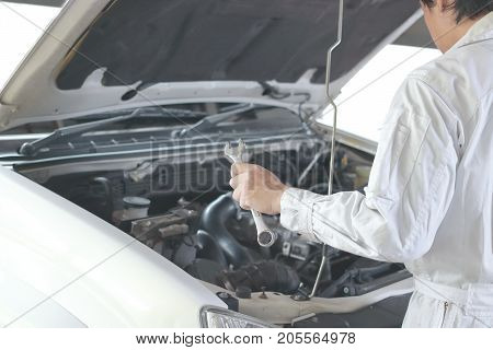 Side view of automotive mechanic in white uniform with wrench diagnosing engine under hood of car at the repair garage.