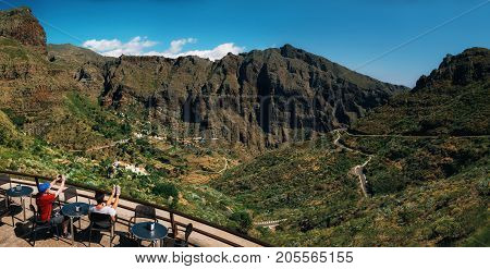 Masca Tenerife Canary islands Spain - May 25 2017: Panoramic view of Masca valley. Tourists are in cafe on mountain pass and admire Scenic mountain landscape.