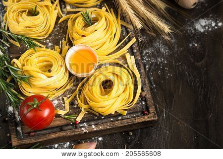 Fresh raw pasta tagliatelle and ingredients for cooking at dark wooden table. Italian food background.