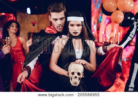 Halloween party. A guy in a vampire costume and in a raincoat is behind a girl in a sexy nun costume. The monk is holding a human skull in his hands