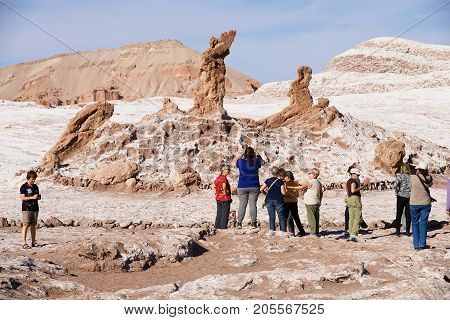 SAN PEDRO DE ATACAMA, CHILE - NOVEMBER 24, 2013: Unidentified tourists visit Las tres Marias (Three Marys) formation rocks in Valle de la Luna in San Pedro de Atacama, Chile.