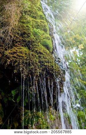 Photo of little beautiful waterfall flowing in cave