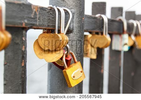 Lock as a symbol of eternal love. Metal locks on the railing of the pier in the Baltic Sea