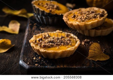Thanksgiving day concept with homemad pumpkin tartlet, mini pie, on wooden background. Healthy autumn food.
