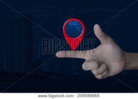 Map pin location button on finger over world map and modern city tower Map pointer navigation concept Elements of this image furnished by NASA
