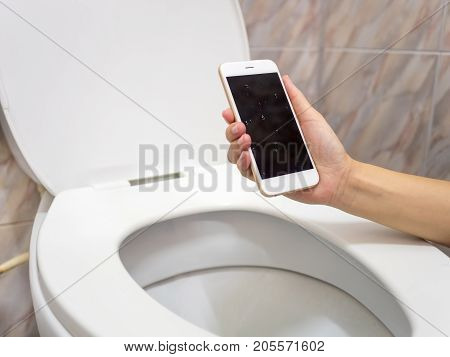 Human hand holding wet smart phone in water closet. Water damage waterproof concept.