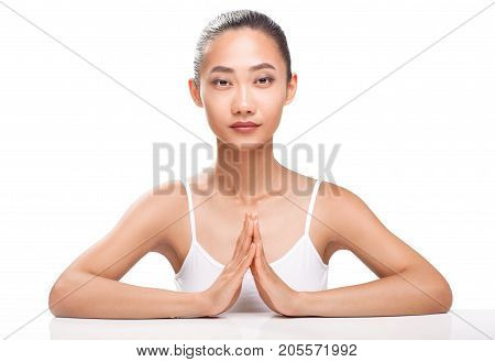 Young Asian Girl With Hands Folded In Harmony Symbol