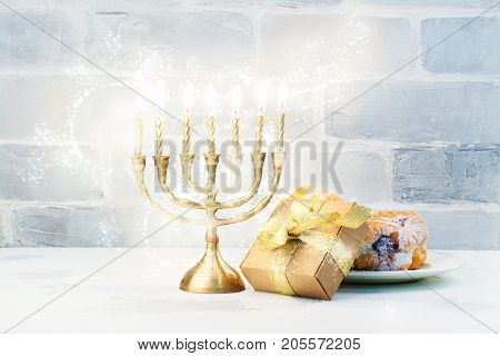 Happy Hanukkah background with menorah, burning candles and donuts. Space for text