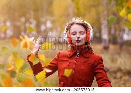 Young woman with headphones dancing in autumn park. Girl listening music in headphones.