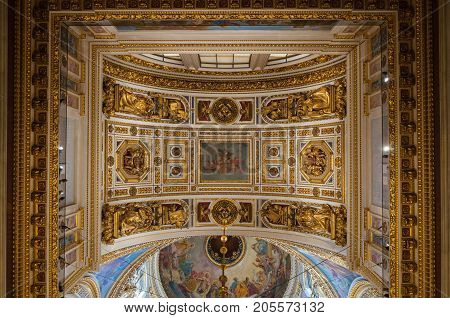 SAINT PETERSBURG RUSSIA - AUGUST 15 2017. Ceiling decorated with sculptures and Bible paintings in the interior of the St Isaac Cathedral in Saint Petersburg Russia. Inside view of Saint Petersburg Russia landmark
