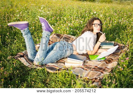 Young Girl With Book Outside In Summer Day
