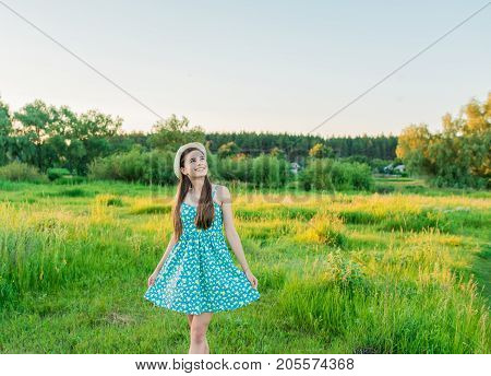 Smiling woman with bouquet of wildflowers in a field with green grass and blue sky. Beautiful teenage girl with brown long hair in short dress on the field