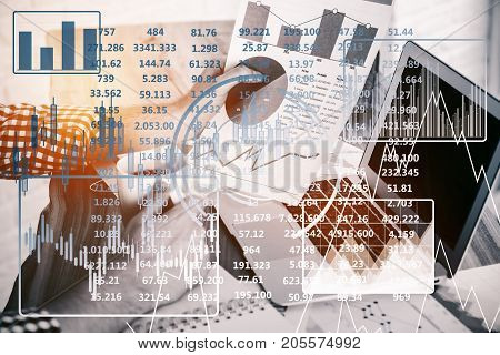 Side view of businessman drinking coffee and doing paperwork at workplace with laptop and abstract digital business screen. Analytics concept. Double exposure
