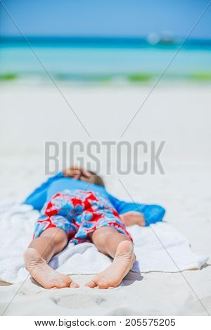 Little feet of boy relax on summer tropical white beach