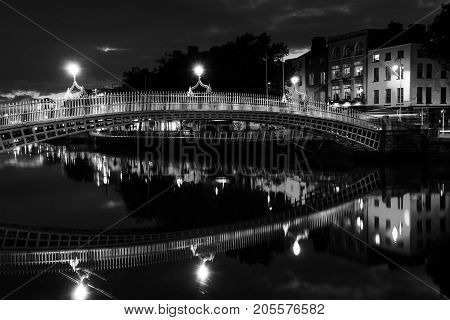Night view of famous illuminated Ha Penny Bridge in Dublin, Ireland with reflection in the river. Black and white