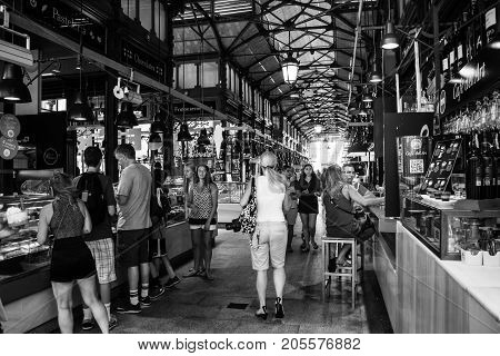 MADRID, SPAIN - JULY 22, 2015: People eating at Mercado San Miguel, which is one of the most popular places in the city of Madrid, Spain. Different food stalls, drinks, seafood. Black and white