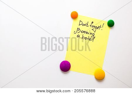 Fridge note with the text: Don't forget! Booking a hotel