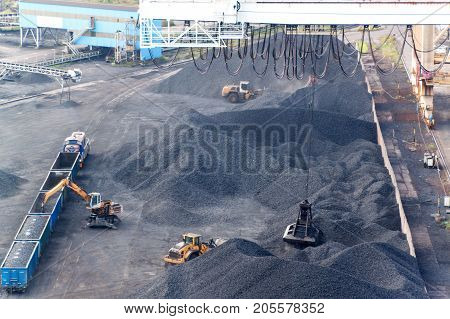 Work in port coal transshipment terminal. Coal unloading of wagons with special cranes. Working in a port near the Baltic Sea