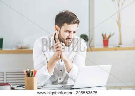 Portrait of young caucasian male using laptop computer in modern office. Project occupation work communication concept