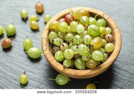 Ripe gooseberry in a wooden plate and scattered next to a plate on a black slate background space for text. Gooseberry multicolored