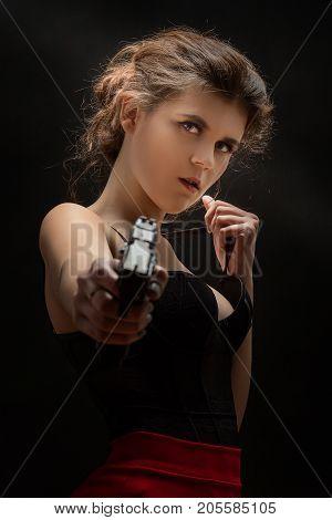 beautiful young woman with black gun aiming at camera