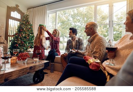 Family sitting together in living room on christmas eve. Family with little girl celebrating christmas festival at home. Woman putting a crown on her daughter's head.