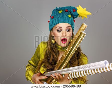 Woman Isolated On Grey Catching Falling Wrapping Paper Rolls