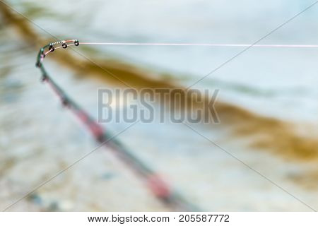 fishing feeder rod with a tight line indicates a bite. Shallow depth of field, soft focus. Focus on the rod tip